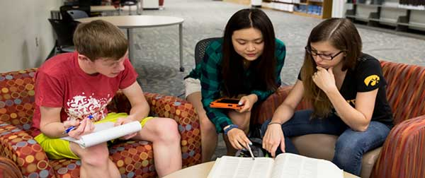 Three students sit and collaborate while sitting in comfy chairs surrounding a low table.