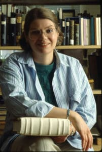 Pamela Spitzmueller holds a book with wooden boards and alum taw leather spine in front of bookshelfs
