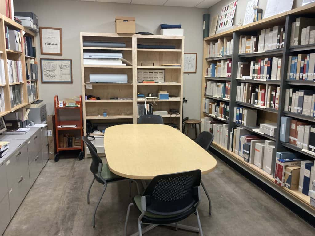 This photos shows the book model collection room with bookshelves of binding models and an oval conference table.