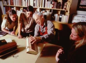 four people looking at a book model on a table in front of shelves with other book models
