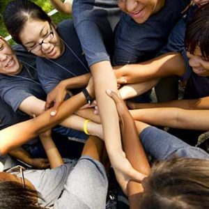 Group of students grasping arms while in a circle.
