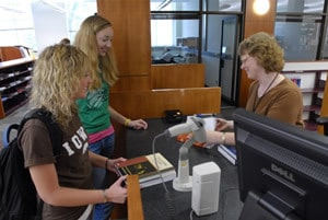 Two students checking out books at the circulation desk in the Engineering Library.