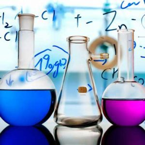 Lab glassware filled with colorful liquids in front of a transparent writing glass.