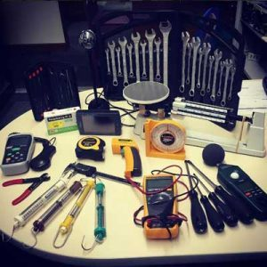An array of hand toos, scales, electronic sensors and other tools laid out on a table.