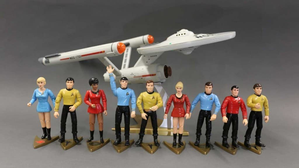 Collectible figures from Star Trek's original series standing in front of a small model of the USS Enterprise, courtesy of Lisa Martincik.