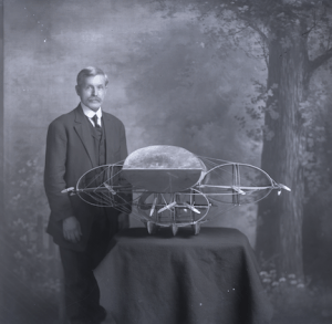 Photograph of Frank Brinton standing next to one of his airship models