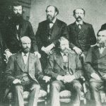 Photo of a group of eight men posing for photo.