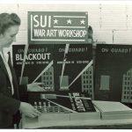 Instructor Alice Davis reviews war art workshop posters, 1942