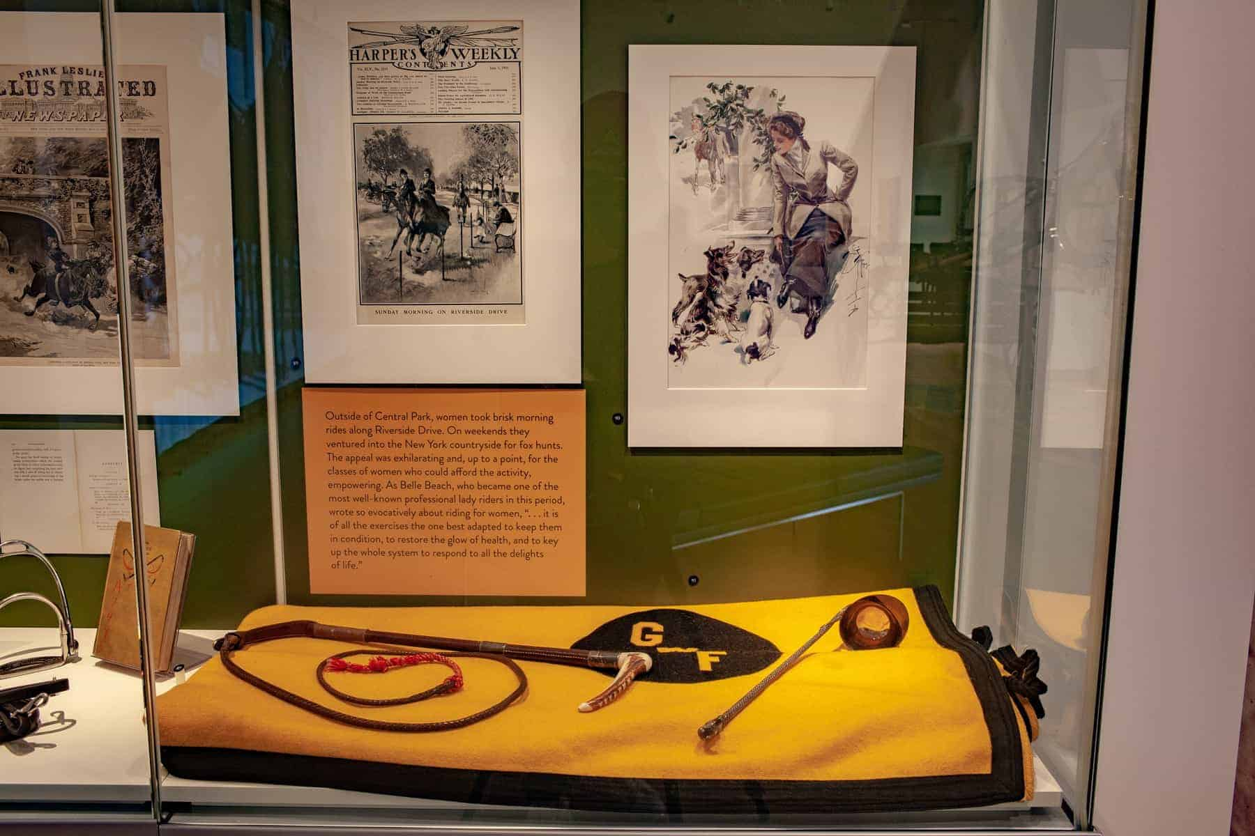 A black and gold horse blanket sits at the base of the case, and over the top are laid a whip and decorative ladle. An illustration of a woman in riding attire posing with dogs is at right, and at left an illustration of women riding on Riverside Drive.