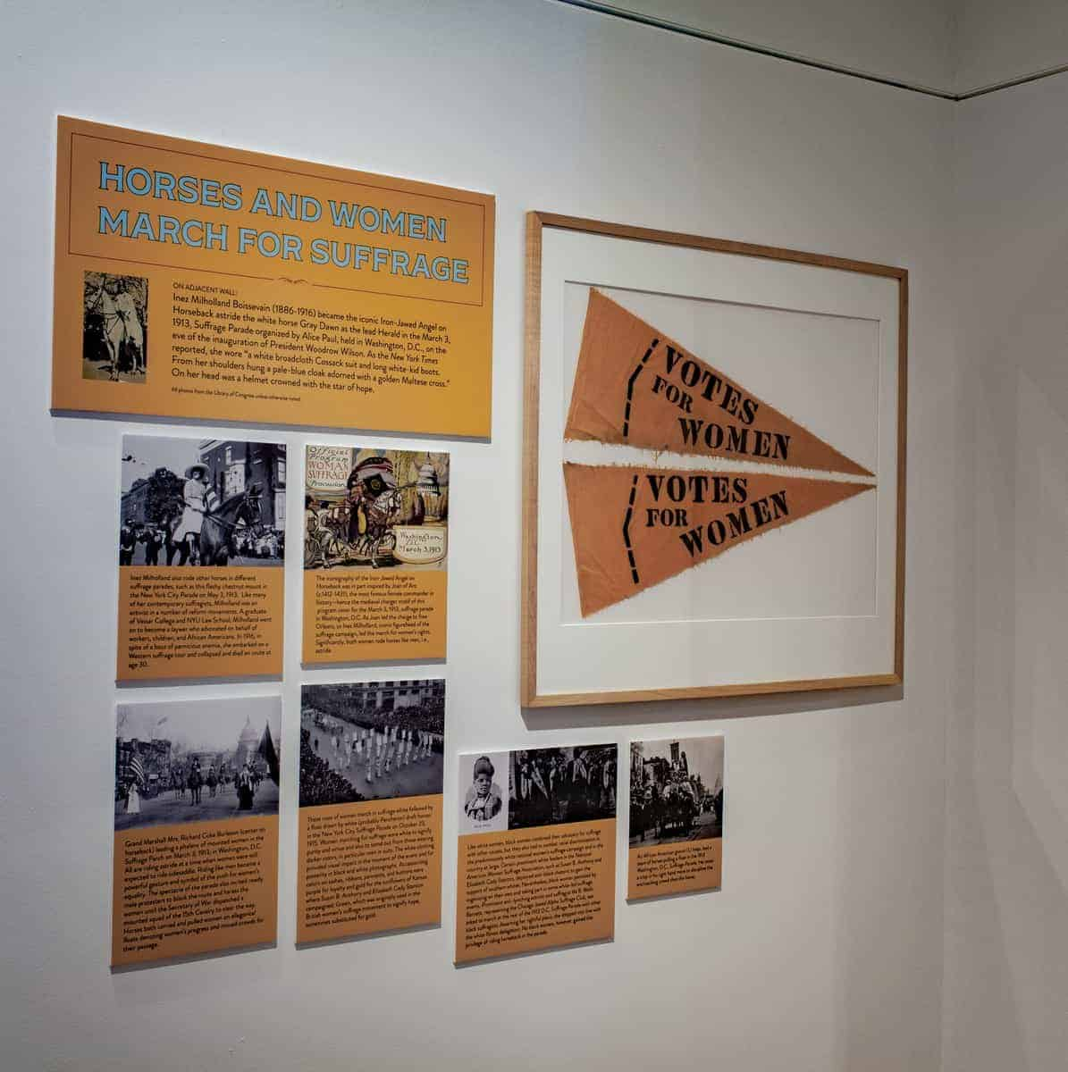 A series of printed panels attached to a white gallery wall show reproduction photographs from the Library of Congress. These images primarily consist of women with their horses in suffrage parades circa 1913. Each image is accompanied by text.