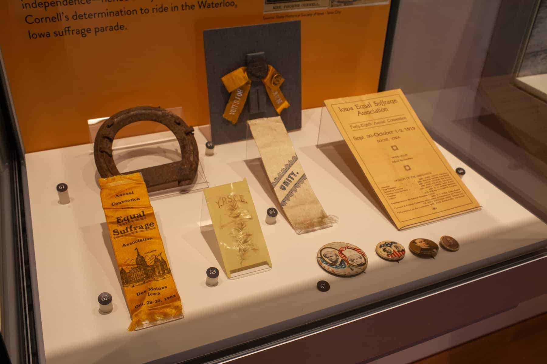 This case has several small items displayed together. Assorted buttons, ribbons for pinning to clothing, a rusty horseshoe, and a flat paper convention program from 1919 are on display.
