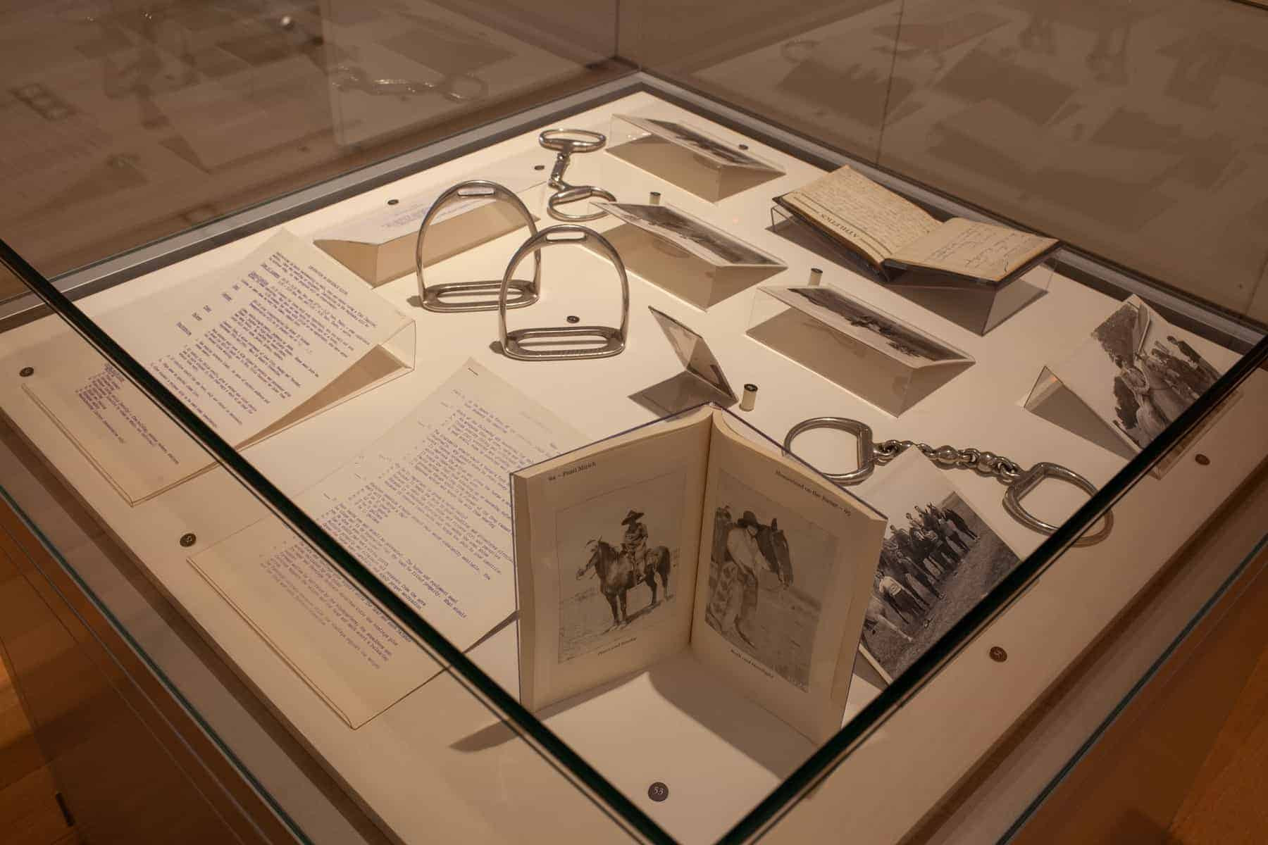 A large, square case in the gallery holds a variety of objects. Photographs and a test related to horseback riding from UI's Women's Athletics Department in the 1950s, bits, stirrups, an autograph book, and a paperback standing vertically.