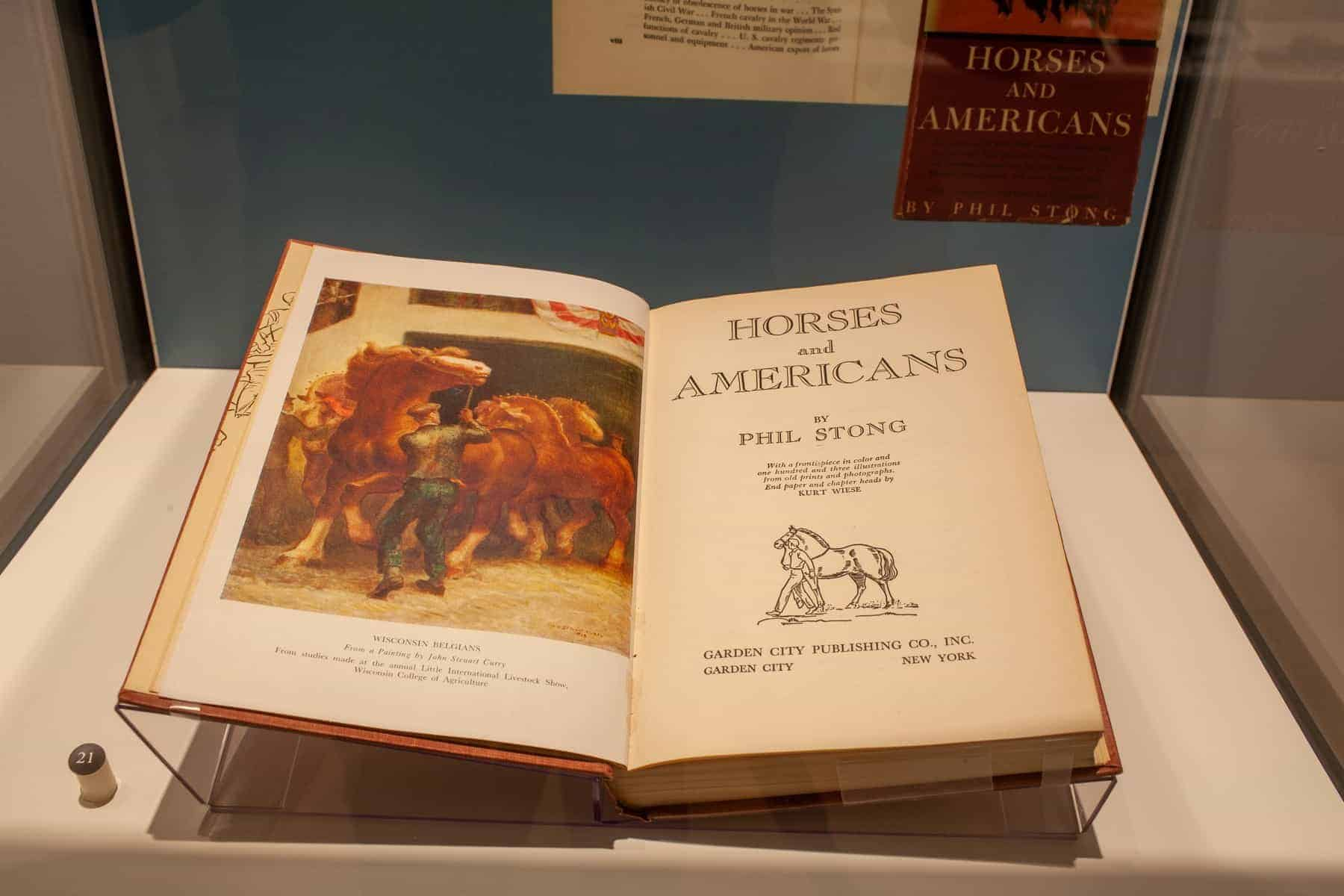This case contains one book. It is open to a colorful illustration of a man with two horses and to the title page.