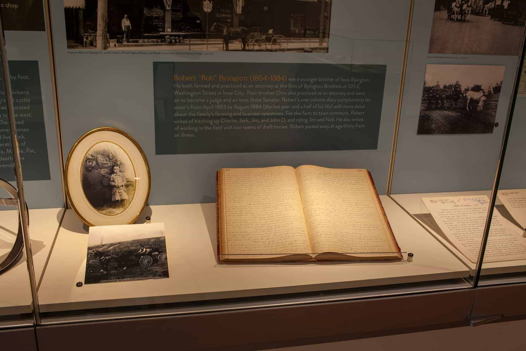 In the case is a 19th century handwritten diary by Robert Byington. The case also includes a photo of a travelling salesman with horse and buggy, and a photo of a young boy with a toy horse.