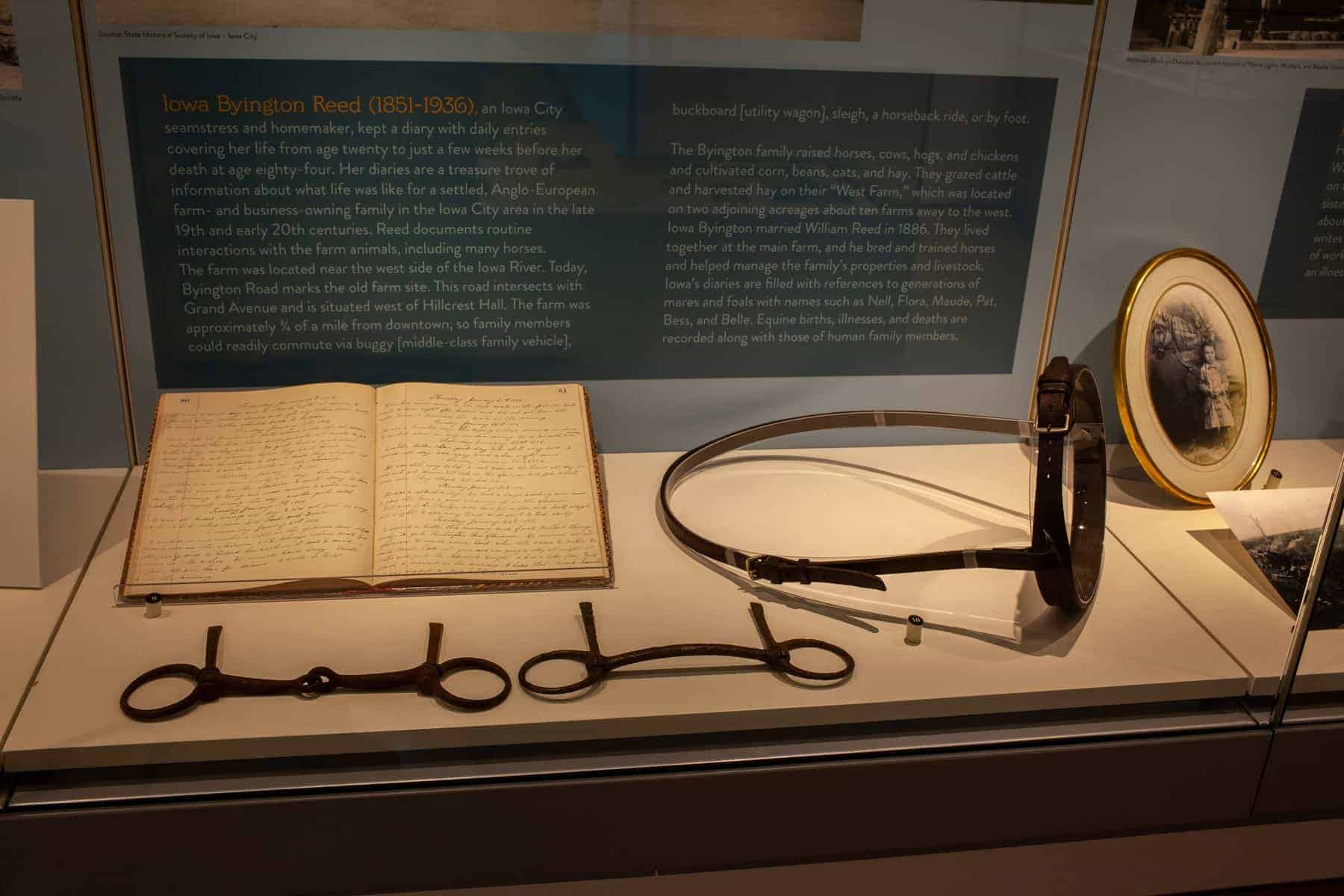 A 19th century diary with beautiful handwritten script is open at the bottom of the display case. Two antique horse mouth bits lie in front of the diary, and to the right is an antique leather horse noseband.