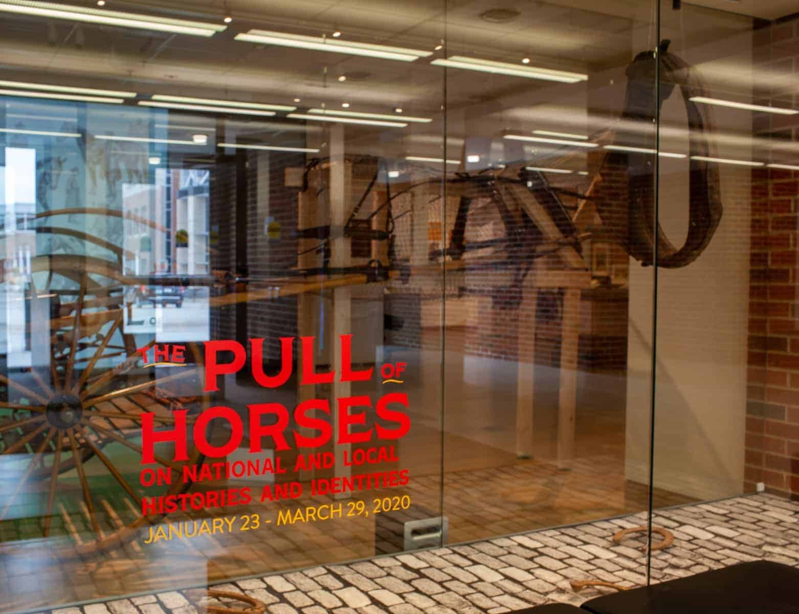 Outside the Main Library Gallery, the front window presented a preview of the exhibition. Printed cobblestone lined the bottom of the window case, and vintage draft horse shoes and a horse collar gave the illusion that an invisible horse was present.