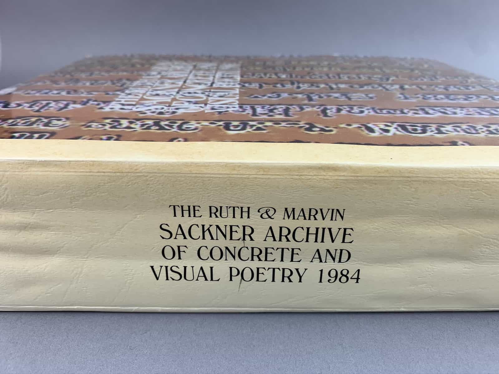 This page includes three images. One is the catalog cover, which is orange with black and white vertical text as design. The catalog title is prominent. The second image is the catalog spine and features the title. The third image is the open catalog.