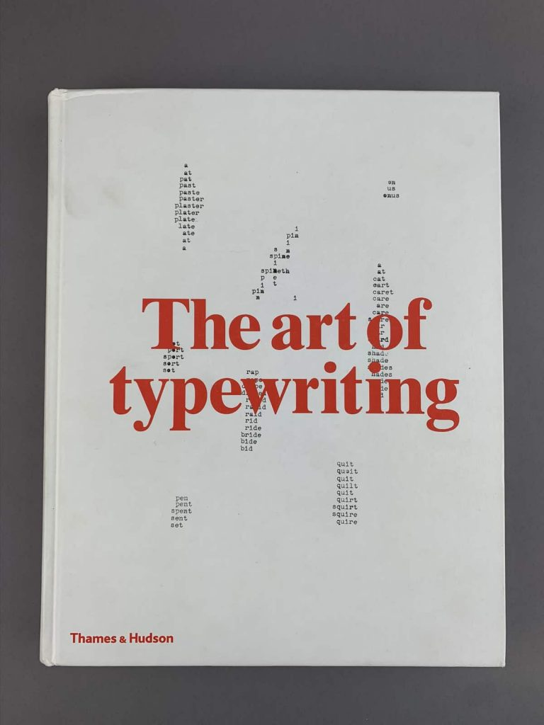 This image is of a white book cover with red text which says The Art of Typewriting.