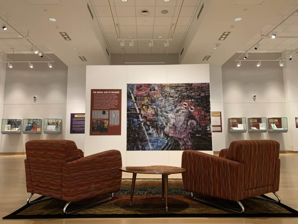 Two chairs face a mural and the open gallery. Six cases of objects are visible in the photo.