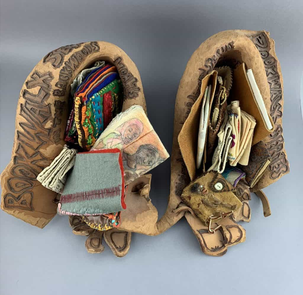 Two leather shoe-shaped objects hold numerous small books made with papers, fabrics, beads, thread, and more. The books and art pieces are colorful.
