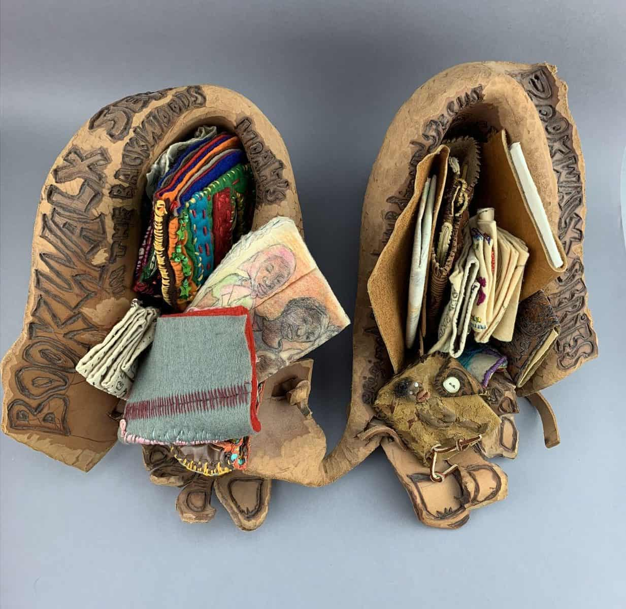 There are two photos on this page. The first is of a set of leather shoe-type objects which cradle several small, varied artist books made of paper and fabric. The second is a view from behind the leather shoes. Leather lacing holds the shoes together.