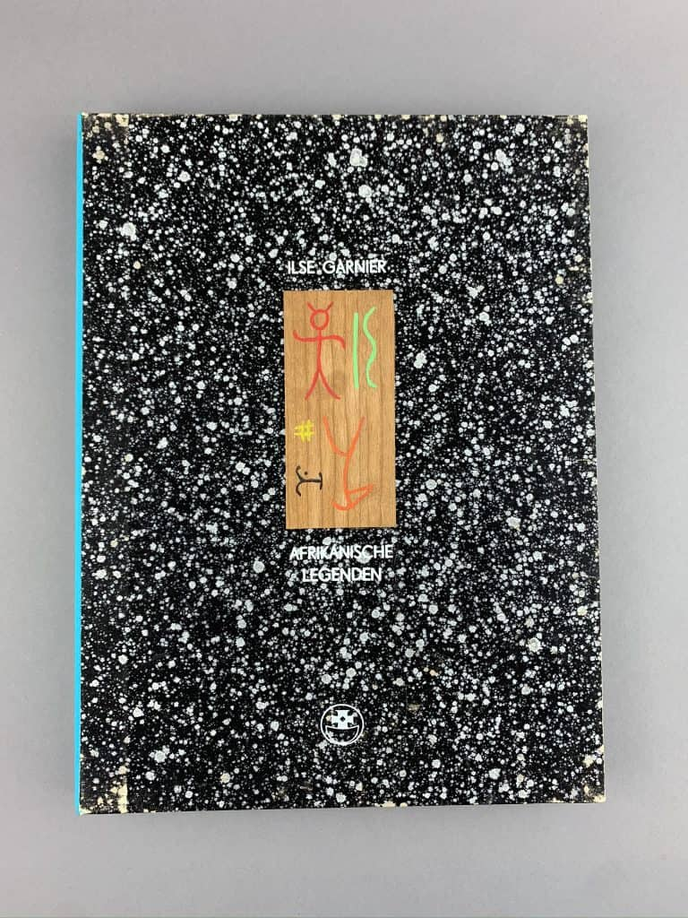 A black and white spatter pattern graces the cover of this piece, with an aquamarine spine. It says Ilse Garnier, Afrikanische Legenden. This is German for African Legends.