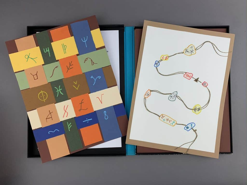 A piece with colorful woven paper strips and African symbols sits on the left side of the photo. On the right is a multimedia piece of drawn beads and African symbols. The string holding the beads together is drawn in some areas and consists of real string in others.