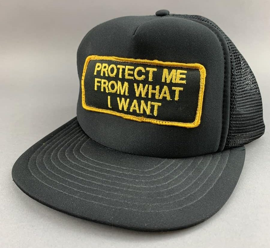There is one photo on this page, and it is of a black hat with a black patch. Yellow embroidered text and border feature on the patch, which says Protect Me From What I Want.