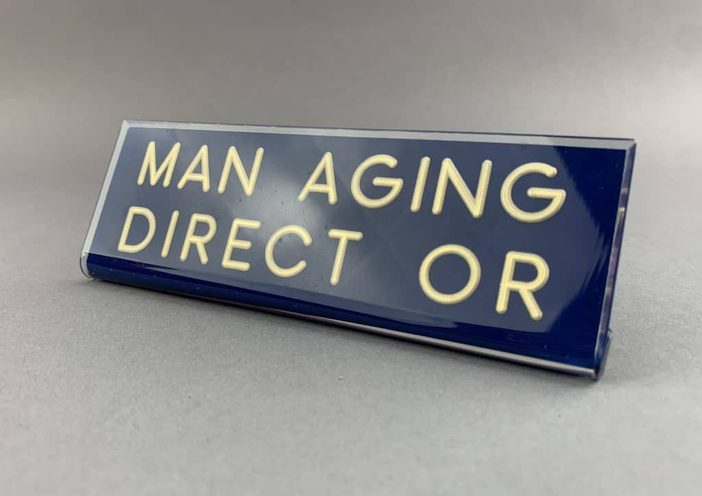 """A blue engraved plexiglass desk nameplate says """"Man Aging Direct Or,"""" a play on the job title """"managing director."""""""