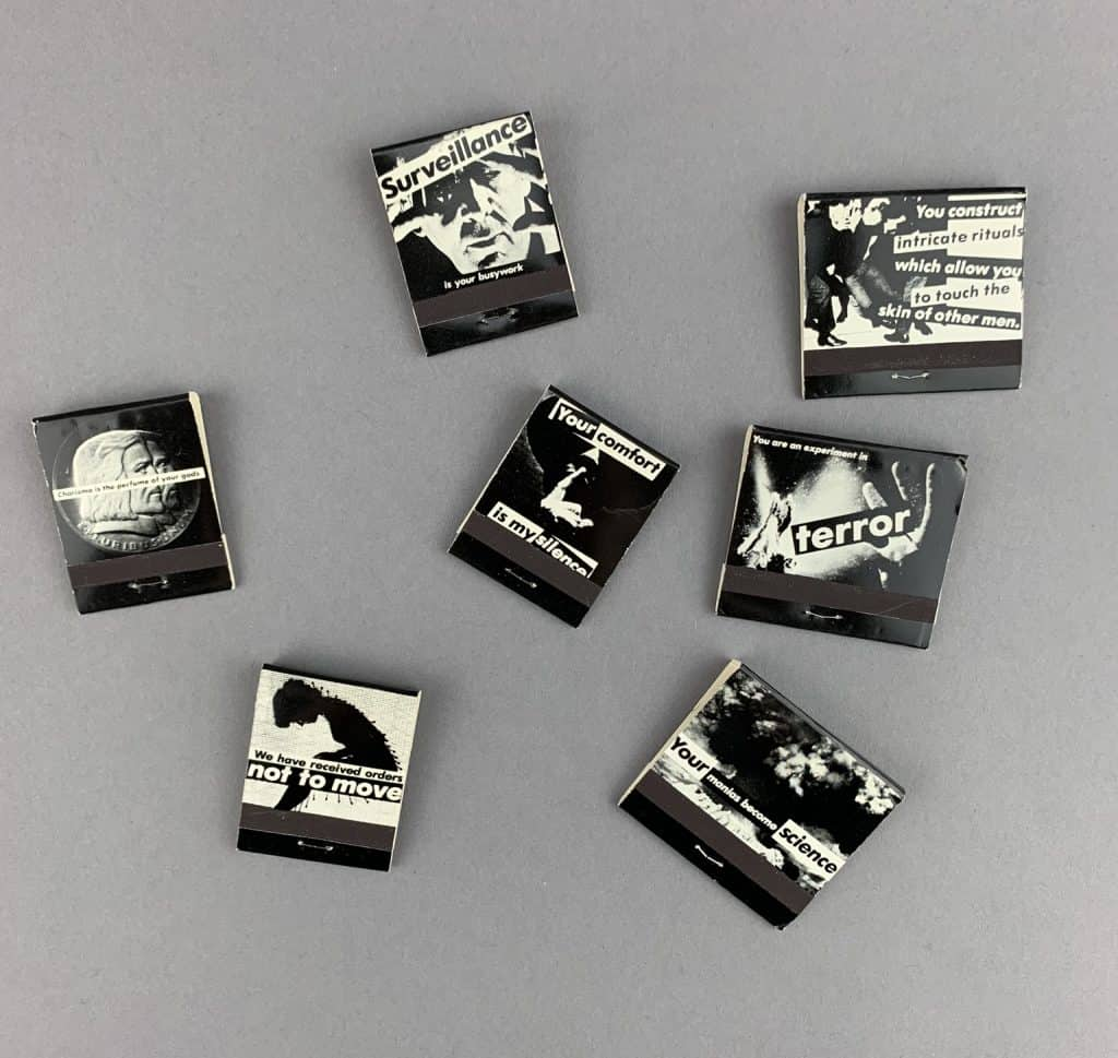 """7 black, white, and gray matchbooks lie together on a surface. Each has a unique message. For example: """"We have received orders not to move,"""" """"your mania becomes science."""" """"your comfort is my silence."""""""