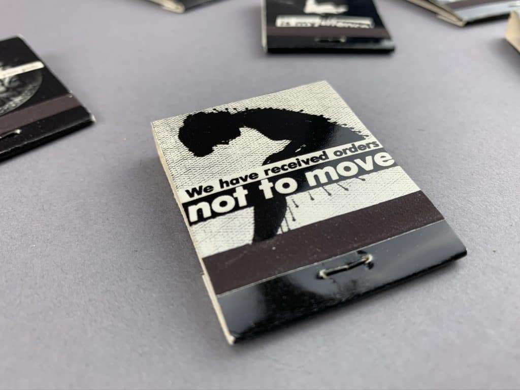 """Matchbook that says """"we have received orders no tot move."""" An illustration of a womans silhouette full of pin needles."""