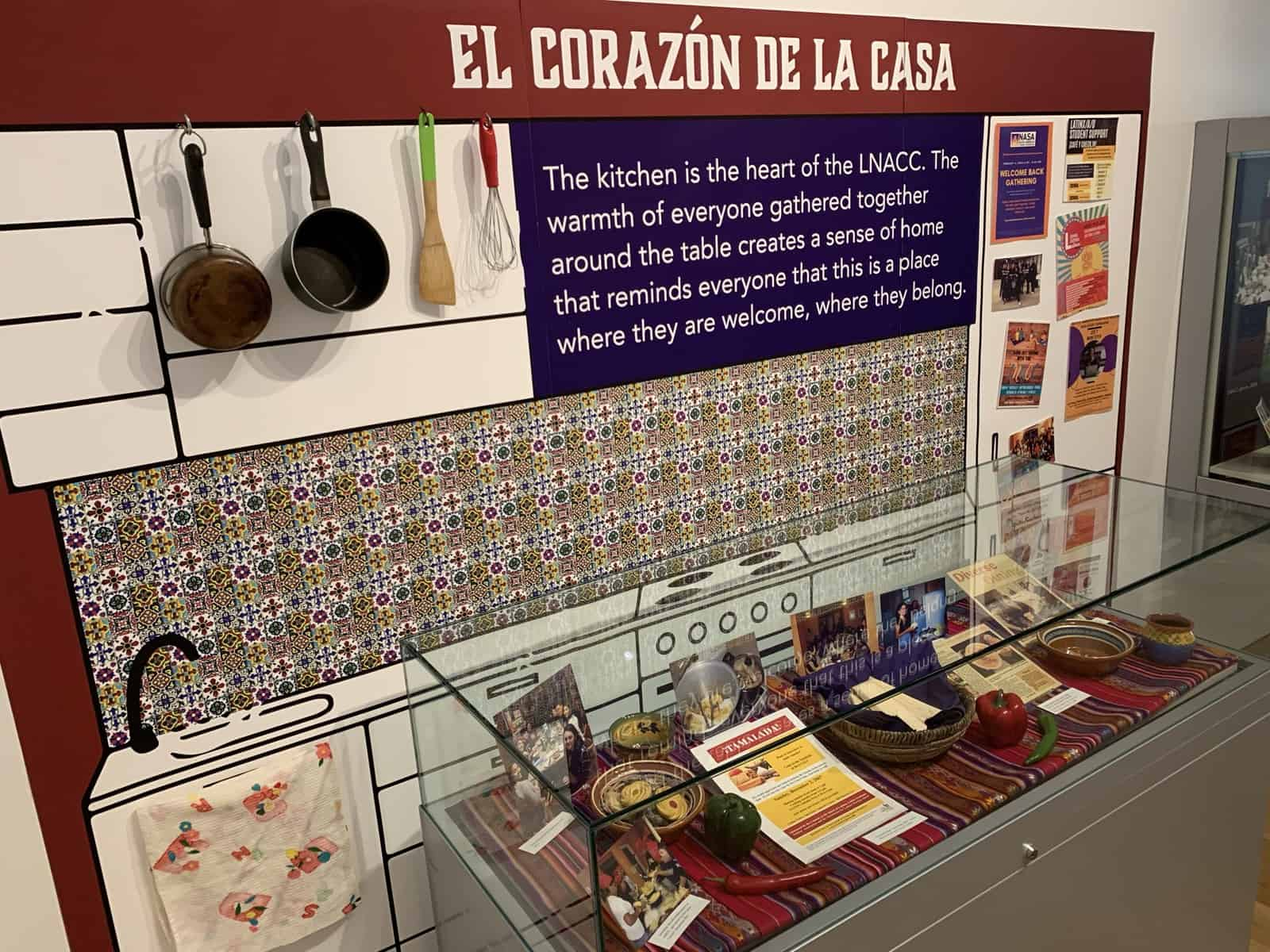 A small kitchen scene in the exhibit that includes a 2D kitchen background and an exhibit case filled with photos of LNACC students eating and cooking. Faux tamales, peppers, and cookies are included.