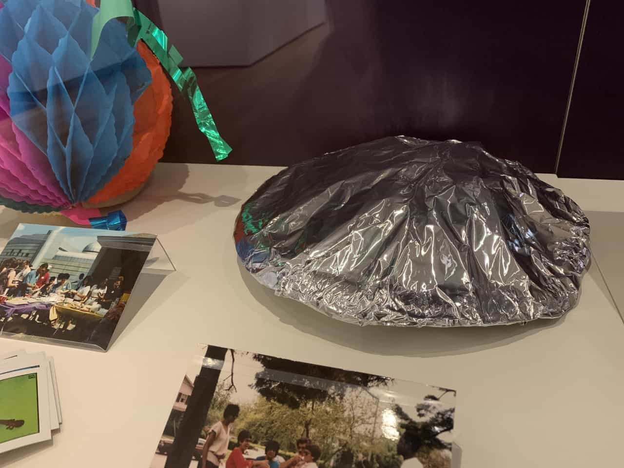 An aluminum foil-wrapped plate sits in a gallery case, reminiscent of a to-go plate from a family gathering.