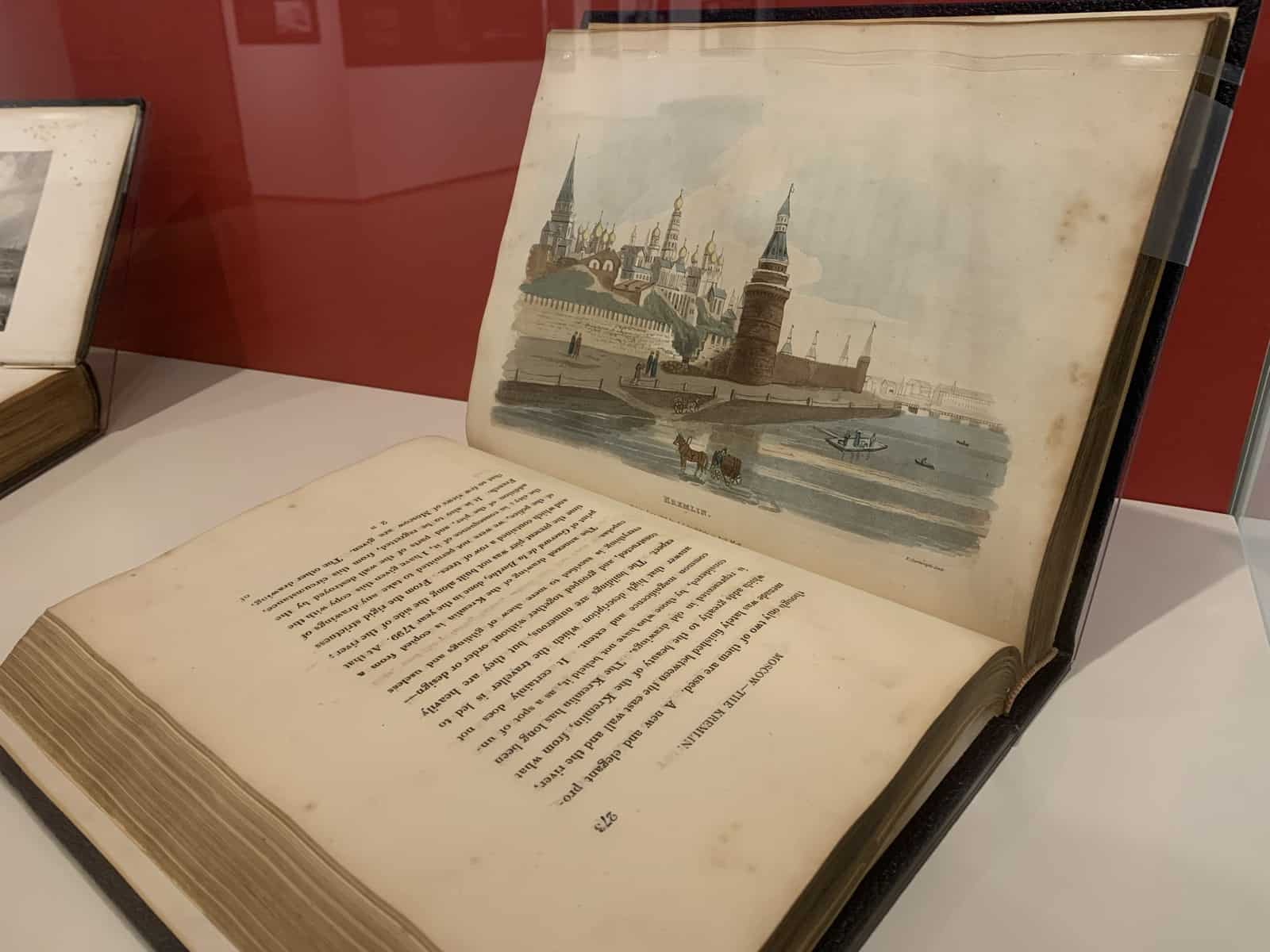 The book is open to a color illustration of the Kremlin. The Kremlin has several tall spires and sits along a riverfront.