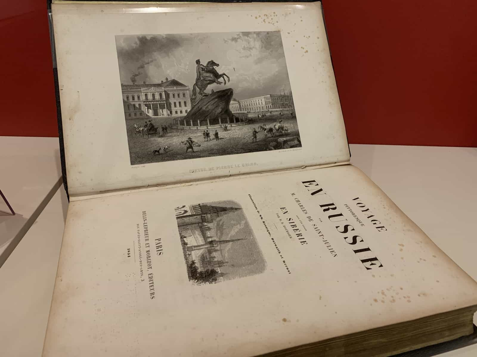 The book is open to its title page. An illustration of the equestrian statue of Peter I in Saint Petersburg is opposite.