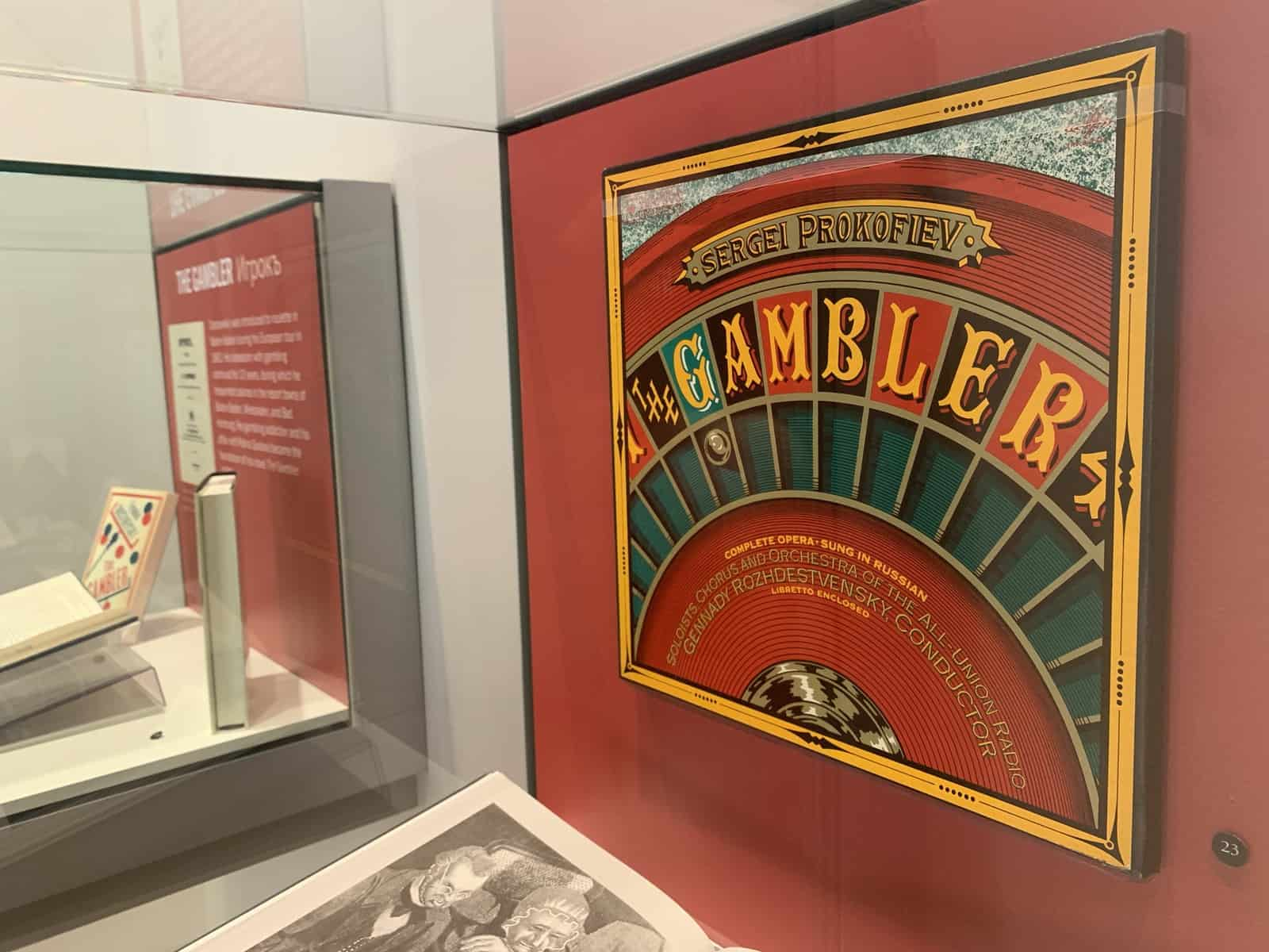A vinyl record box is mounted to the back of an exhibit case. It says The Gambler, and is from the Prokofiev opera. The design features a roulette table.