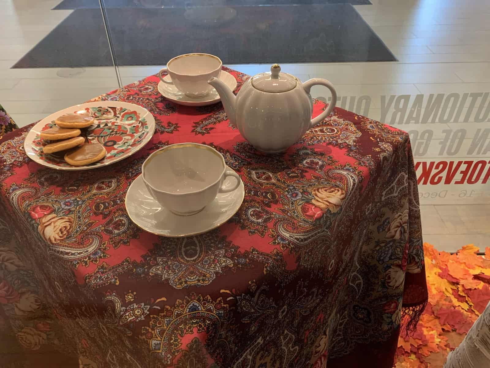 A table draped with Russian scarves sits on a bed of fallen maple leaves. On the table are two white teacups with saucers, a small white teapot, and a plate decorated with an ornate folk-style rooster. Four small faux pancakes are on the plate.
