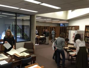 Color photograph of several people looking at books in an exhibit in the John Martin Rare Book Room at Hardin Library.