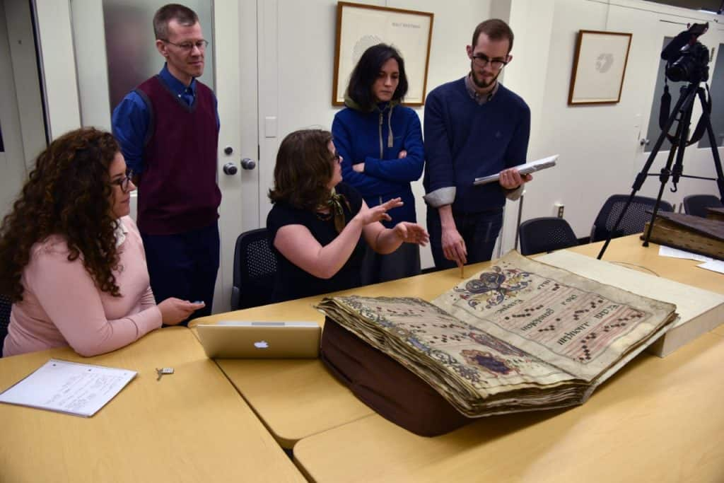 Students examine a manuscript in Special Collections.