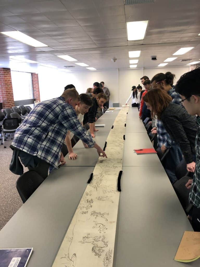 """Students visiting Special Collections & Archives examine a facsimile of """"The Scroll of Frolicking Animals,"""" also known as the Chōjū-giga."""
