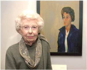 Leola Bergmann in front of her portrait of May Brodbeck in the Iowa Women's Archives, University of Iowa, Iowa City, Iowa, Mar. 4, 2002