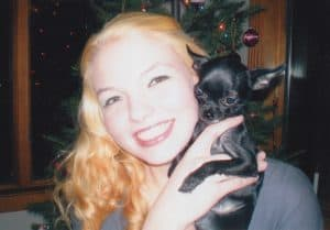 Megan May Bohlke smiling and holding a small puppy, December 20, 2007. Image courtesy of the Bohlke family.