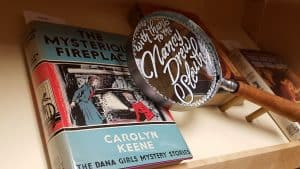 """A magnifying glass propped on the display shelf that says - """"With thanks to the Nancy Drew Sleuths"""". Created by Nancy Romalov and Cheryl Jacobsen."""