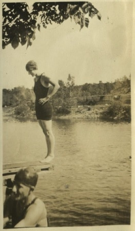 Photo of Mildred standing backwards at end of diving platform  preparing to dive into the Iowa River, ca 1920s.