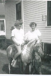 Mildred & daughter, Peggy, outside. Peggy is sitting on a pony. 1950s.