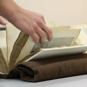 Person looking through an illustrated manuscript
