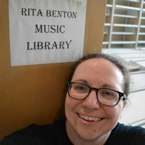 Music librarian, Katie Buehner, rests in front of a book cart labeled 'Rita Benson Music Library' during the move.