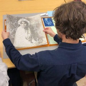 Student looking at paper art