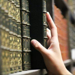 Hand Reaching to a book on a shelf