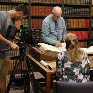 Greg Prickman, head of Special Collections at the University of Iowa Libraries browses through a huge, rare, illustrated tome during the filming of this video.